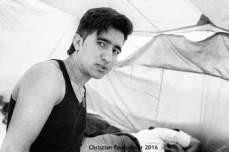 11 – Calais. Jeune Afghan qui m'a demandé de le prendre en photo dans sa tente. Je n'ai malheureusement pas pu lui offrir son tirage car, contrairement au parc Maximilien où je venais tous les jours, mes voyages à Calais étaient plus espacés. Quand je suis revenu, il n'était plus là